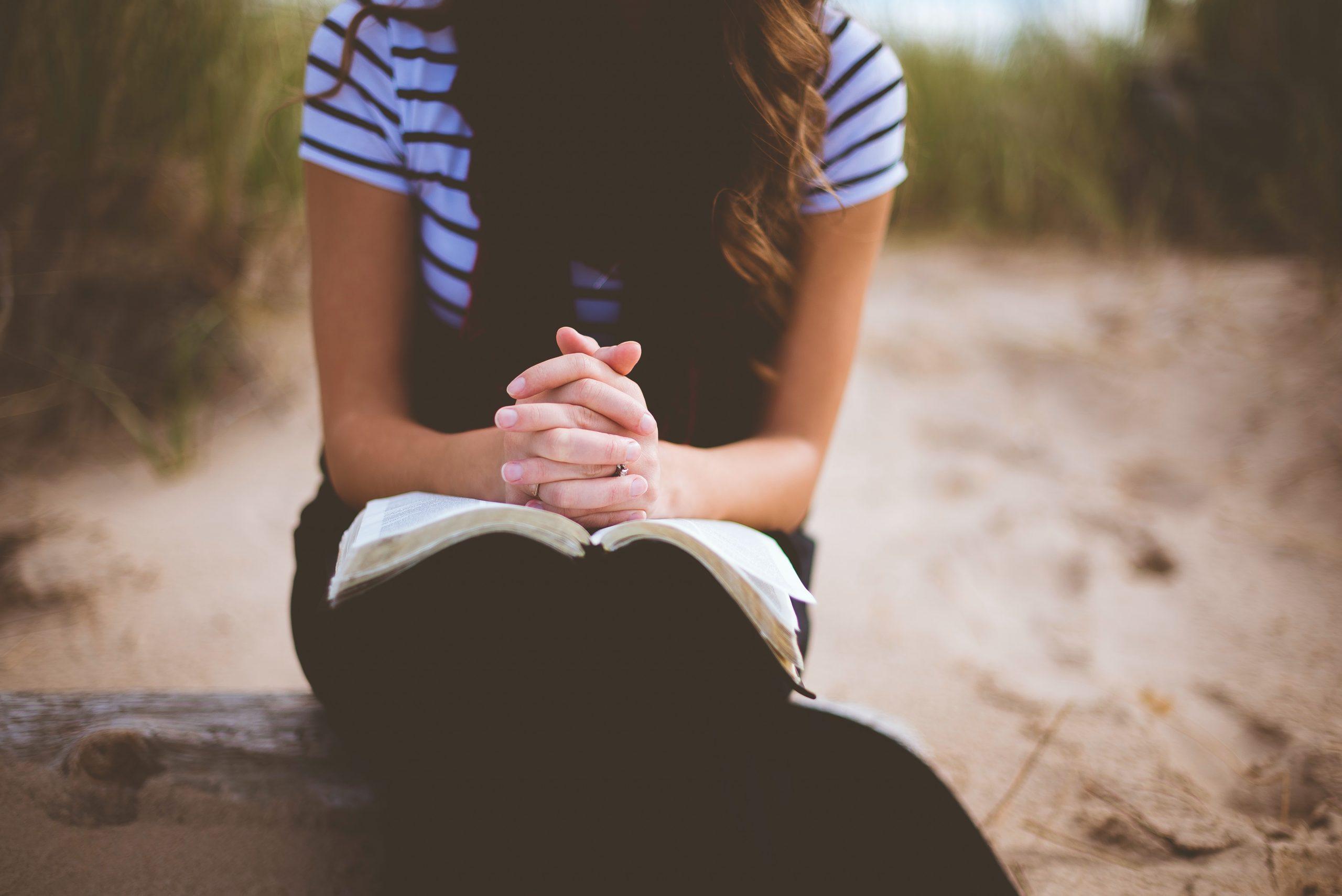 Hiekkarannalla istuva nainen rukoilee Raamattu sylissään.