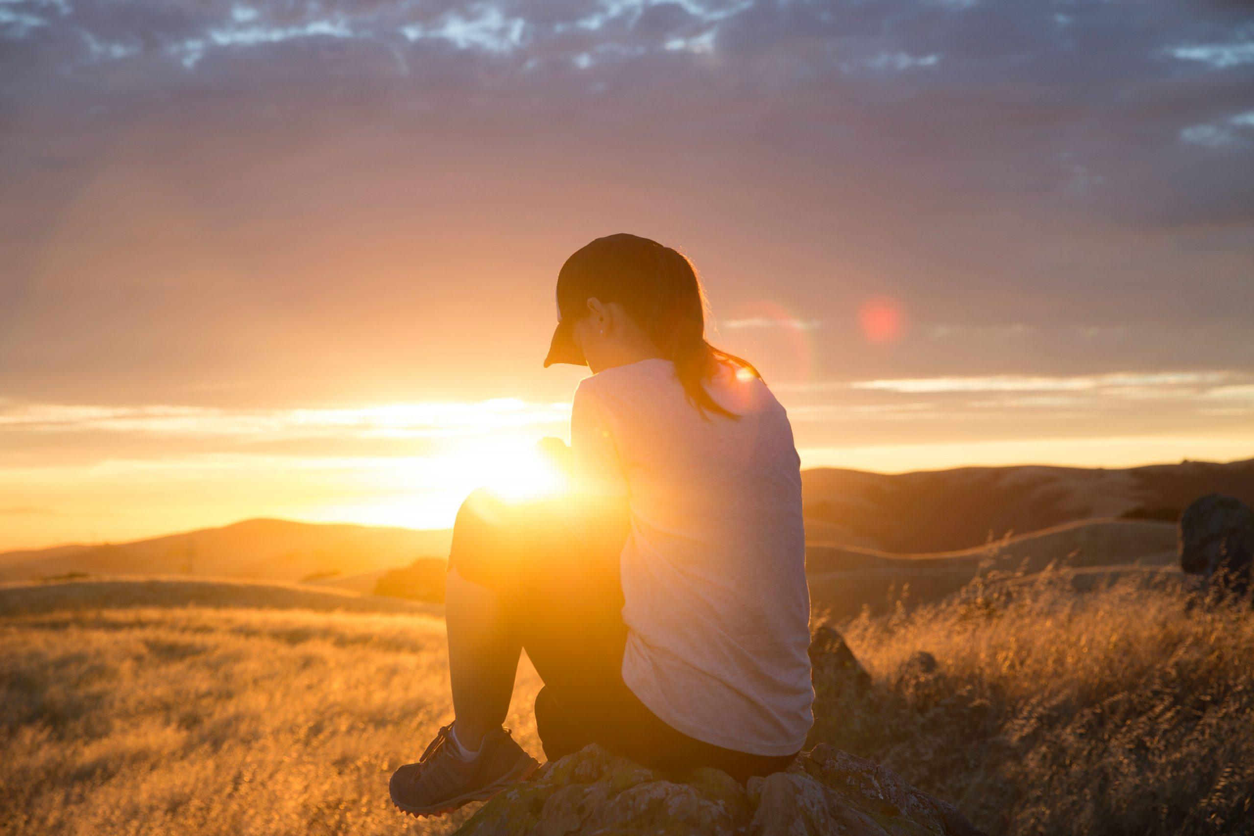 iltaauringossa kivellä istuva nuori nainen