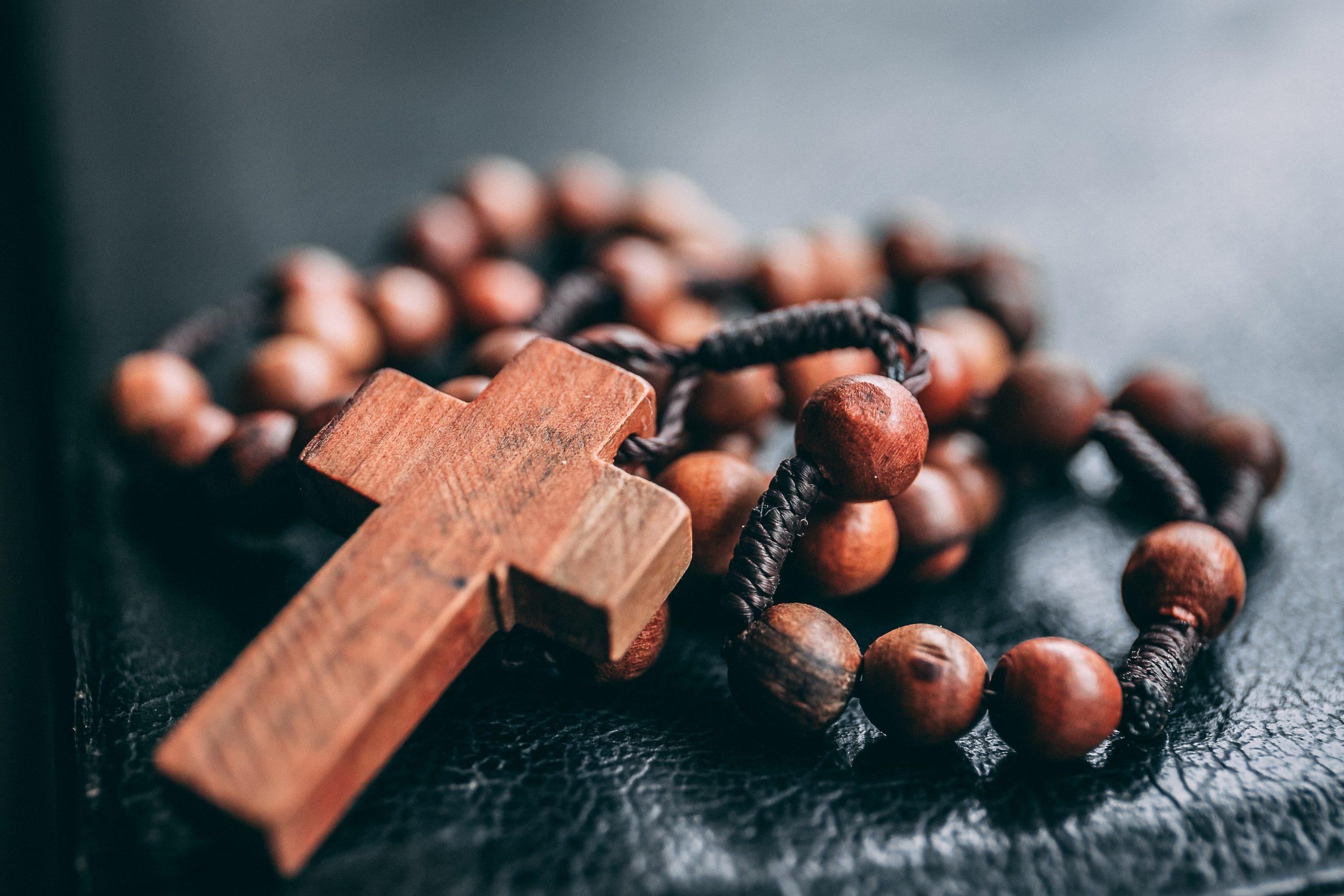 Pöydän kulmalla ruskea risti ruskeiden rukoushelmien päällä.