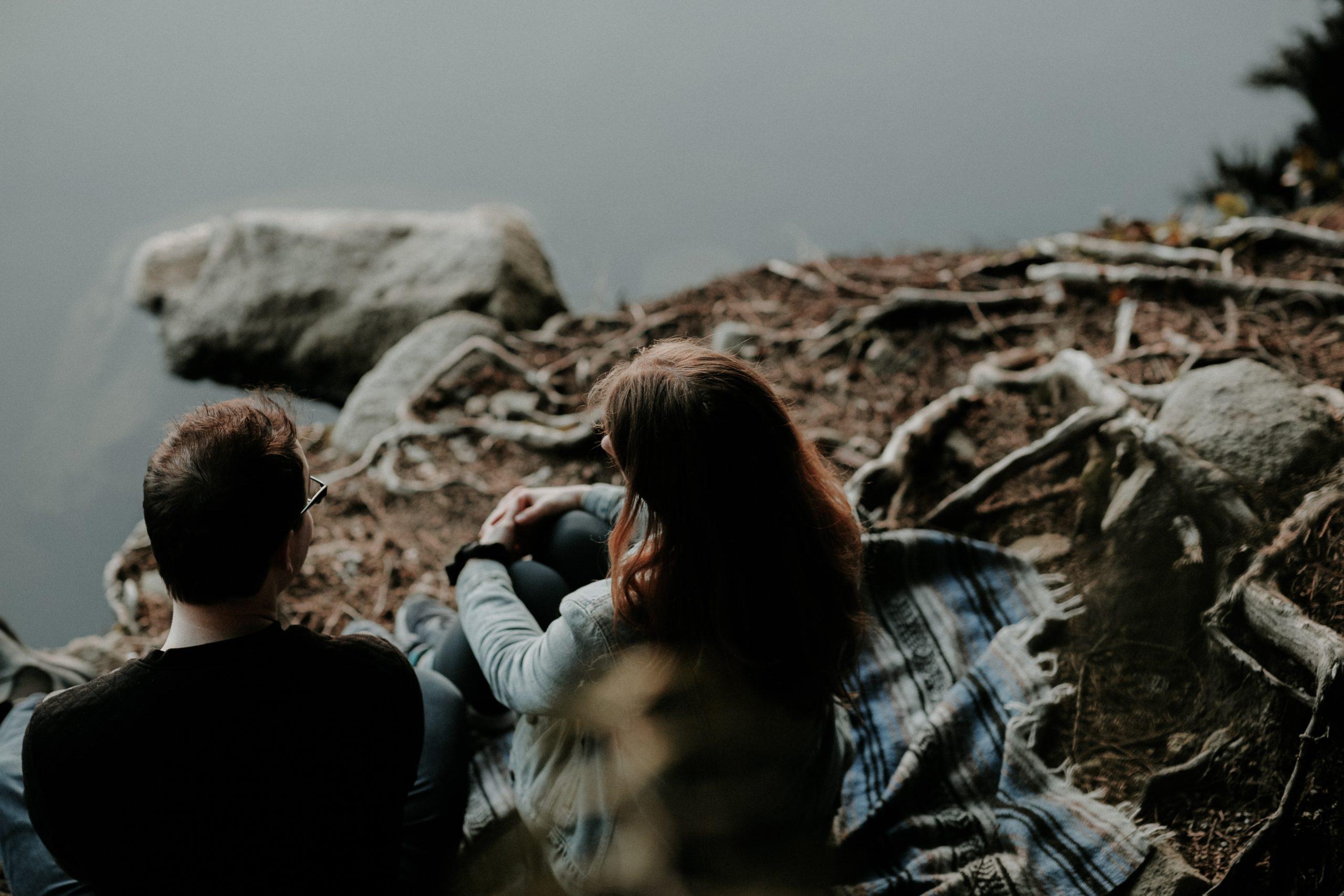 nainen ja mies istuvat kalliolla vierekkäin