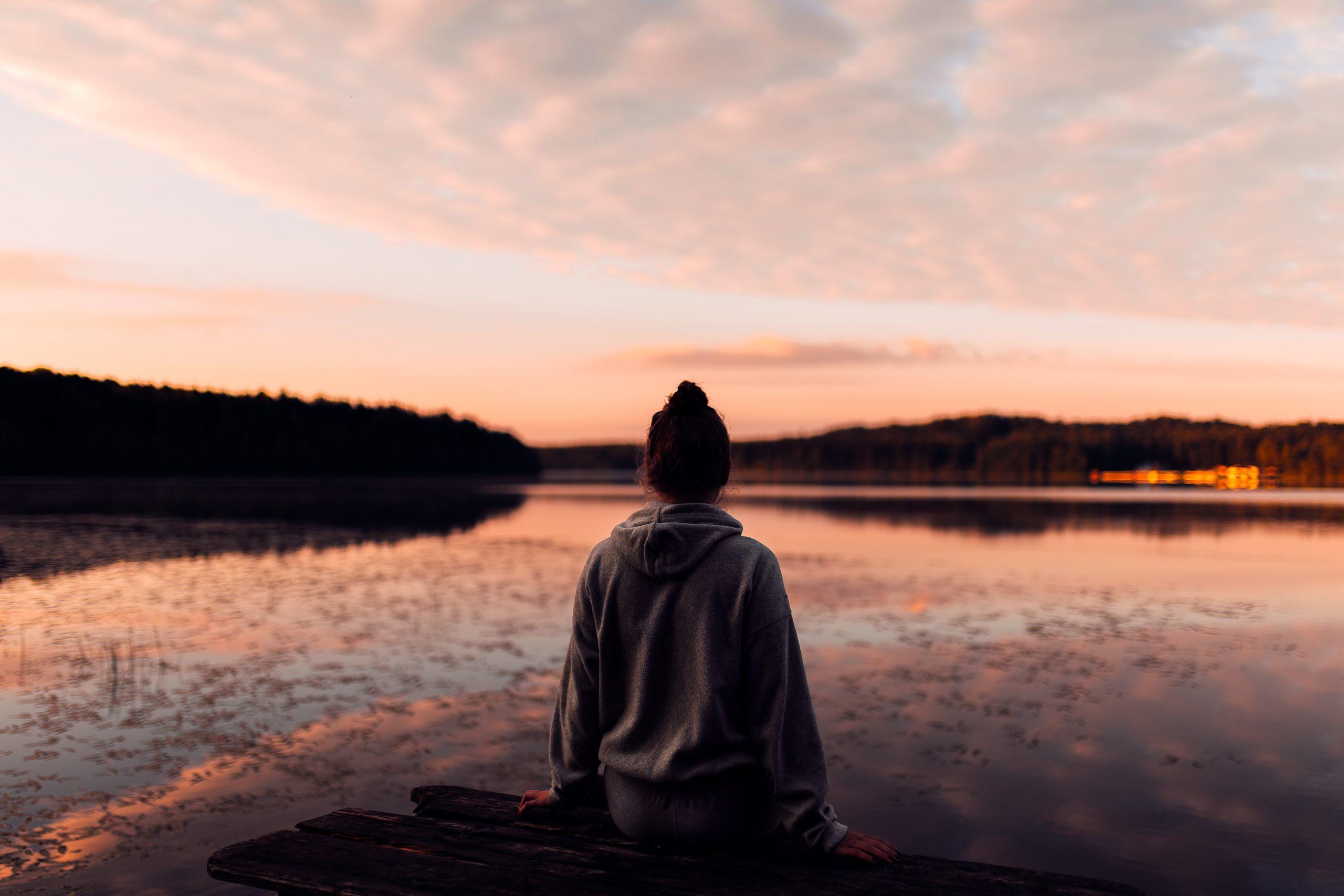 Nuori nainen katselee auringon laskua veden äärellä.