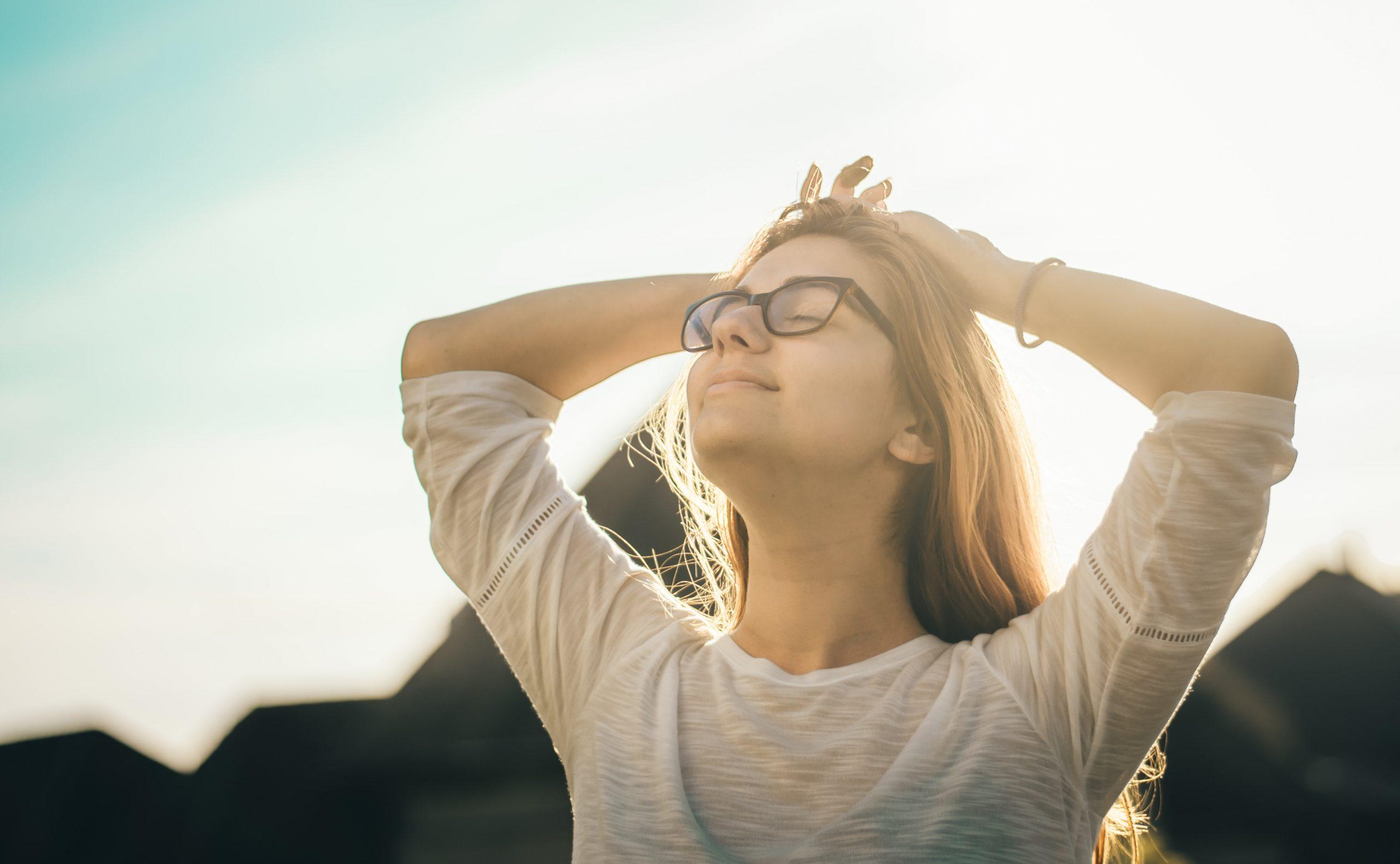 Nainen kädet yhdessä pään takana, silmät suljettuina, seisoo kasvot ylöspäin.