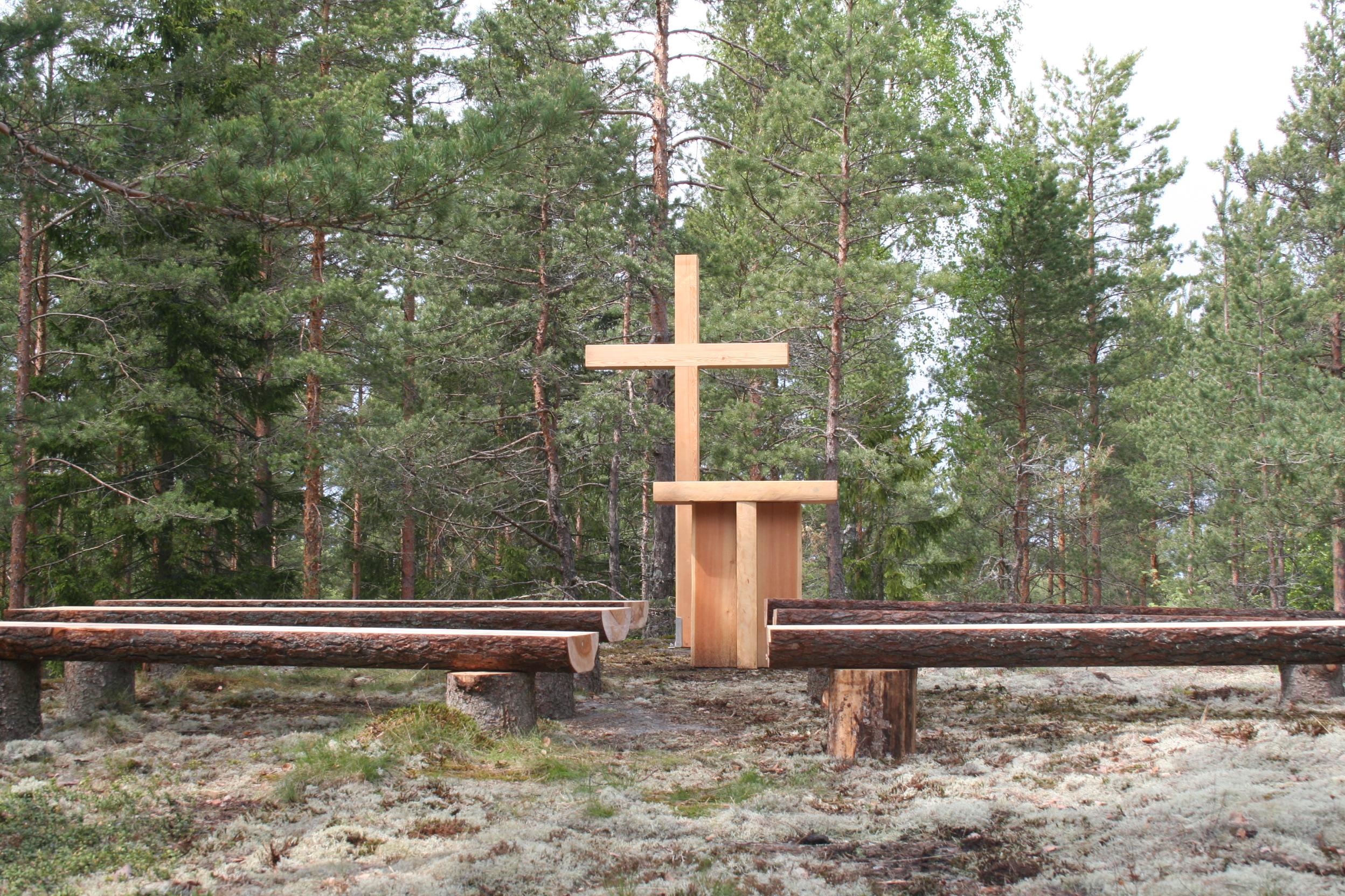 Metsäkirkko, jossa alttari, risti ja puupenkit